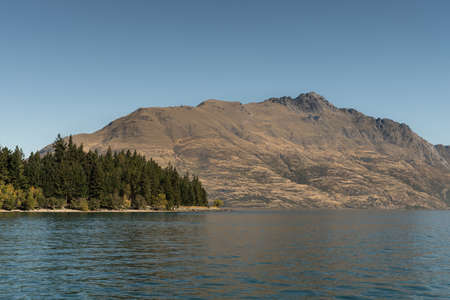Queenstown, New Zealand - March 15, 2017: Brown mountain range with Cecil Peak across dark blue Wakatipu Lake and downtown, under lighter blue sky. Part of green forest fronts the mountain. Stock Photo
