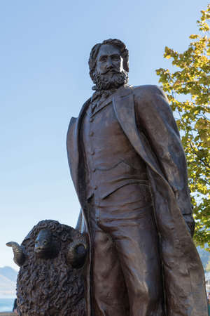 Queenstown, New Zealand - March 15, 2017: closeup of dark bronze statue of William Gilbert Rees, city founder, in downtown against blue sky with some green foliage in back. Sheep holds him company.