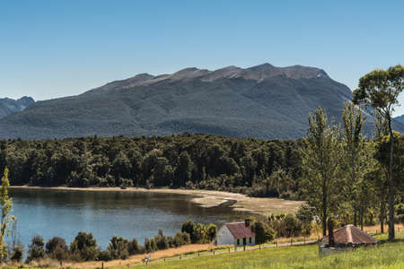 Te Anau, New Zealand - March 16, 2017: shoreline of the lake shows forests and small farm building, now a cottage. Green and yellow grass in foreground, dark mountains in back under blue sky. Stock Photo
