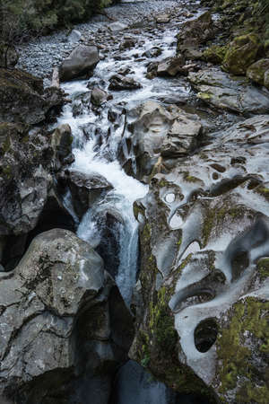 Fiordland National Park, New Zealand - March 16, 2017: River and weird rocks polished and worn out by streaming water at the deep Chasm. Abyss seen, Green moss spots and white water on rocks.