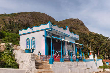 Nilgiri Hills, India - October 26, 2013: Small, sober, blue and white Catholic church feature statues of Jesus and angels. Highland background. Stock Photo