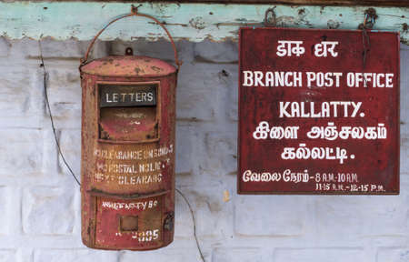 Nilgiri Hills, India - October 26, 2013: Closeup of rusty mailbox and sign at Kallatty Post Office. White writing on red sign in Tamil and English. Gray and light green wall. Editorial