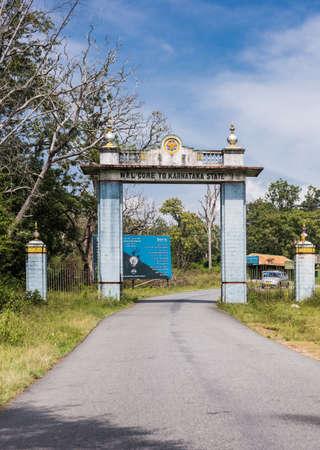 karnataka: Karnataka, India - October 26, 2013: Light blue welcome gate on the state line with Tamil Nadu at Bandipur Tiger Reserve and National Forest. Blue sky, jungle vegetation, narrow road, car and monkey.