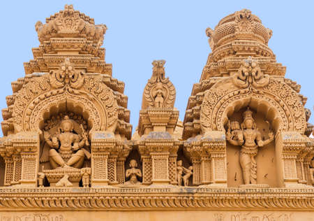 Nanjangud, India - October 26, 2013: Double Niche in beige elaborately decorated sandstone at Srikanteshwara Temple showing both statue of Lord Shiva. Sexual imagery nearby.