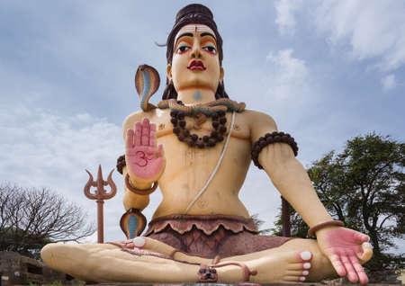hinduismo: Nanjangud, India - 26 de octubre de 2013: Tiro aislado y frontal de la estatua gigante de Lord Shiva del templo de Srikanteshwara contra el cielo azul con las nubes blancas. Multicolor y con serpiente cobra, llamado Vasuki. Editorial
