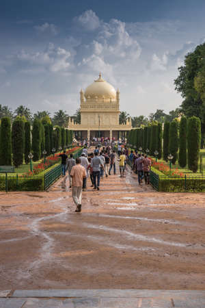karnataka: Mysore, India - October 26, 2013: Green and red park with pathway to cream yellow Tipu Sultan mausoleum with dome under heavy cloudscape. People walking to and from the building. Rain water on path.