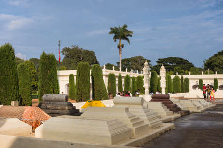 Mysore, India - October 26, 2013: Cemetery with classic Muslim tombs of Generals and Administration top dogs at Tipu Sultan mausoleum under blue sky. Some green vegetation and visitors. Editorial