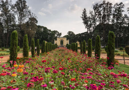 front end: Mysore, India - October 26, 2013: Grounds and green park of Tipu Sultan Summer Palace, named Daria Daulat Bagh. Entry gate to park at end of visual lines. Pink and orange flowers in front.