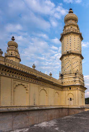 Mysore, India - October 26, 2013: Yellow minaret and wall at Jamia Masjid mosque on Sriranagapatna Island. Doubles as pigeon housing. Blue cloudy sky. Shot from rampart.