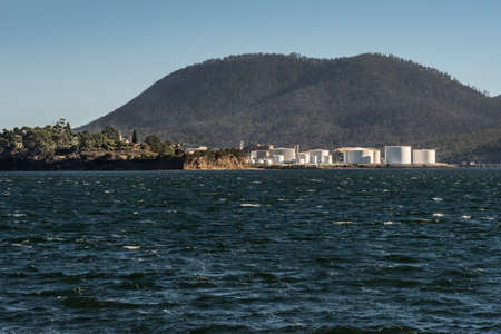 Hobart, Australia - March 19. 2017: Tasmania. The Petroleum harbor with its bright white tanks across Cornelian Bay. Forested mountain in back. Blue sky and blue Derwent River water.
