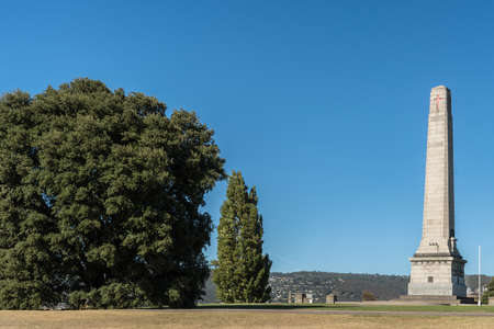 Hobart, Australia - March 19. 2017: Tasmania. Tall white stone Cenotaph war memorial and trees on green hill with trees under blue sky.