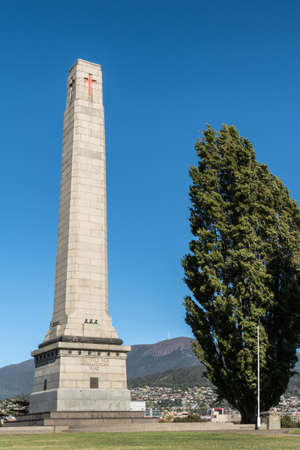 Hobart, Australia - March 19. 2017: Tasmania. Closeup of tall white stone Cenotaph war memorial and tree on green hill under blue sky. Gulf War, Iraq, Afghanistan side. City in back on mountain slope. Sajtókép