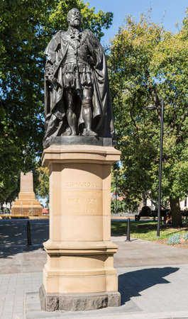 Hobart, Australia - March 19. 2017: Tasmania. Bronze statue on stone pedestal of King Edward VII shows him looking proudly and defiant. Green park background.