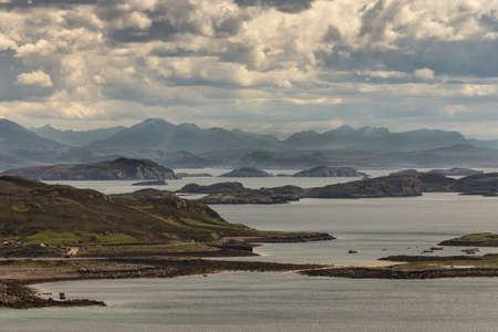 Assynt-schiereiland, Schotland - 7 juni 2012: uitkijken van boven Altandhu gehucht over de Atlantische Oceaan inlaat met een groot aantal rotsachtige eilandjes onder zware stormhemel. Bergtoppen op de rug. Afgemeerde sloepen. Stockfoto