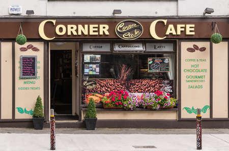 Galway, Irlanda - 3 de agosto de 2017: Cafetería de la esquina de la pequeña empresa con la fachada marrón y beige, la puerta abierta y la ventana de exhibición con las imágenes del grano de café. Foto de archivo - 84694768