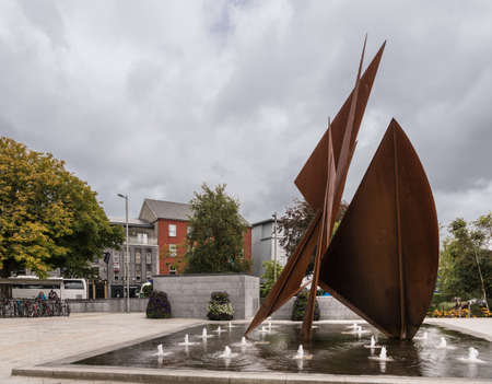 Galway, Ireland - August 3, 2017: Quincentennial Fountain at Eyre Square shows rusty iron plates resembling sails standing in pool. Broader view of square with bus, trees, flowers and people.