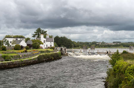 Galway, Ireland - August 3, 2017: The speed and volume of the fast flowing Corrib River is controlled by a dam system upstream of the city. Cloudscape, trees, white water and 1899 office in park.
