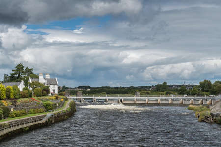 Galway, Ireland - August 3, 2017: Speed and volume of the fast flowing Corrib River is controlled by a dam system with floodgates upstream of the city. Cloudscape, trees, white water and 1899 office.
