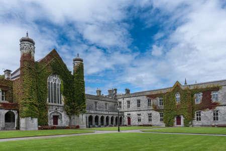 Galway, Ierland - 5 augustus, 2017: Een deel van historische Vierhoek op Nationale Universiteit van de Campus van Ierland. Quadrangle gebouw bedekt met klimop met twee torens onder de blauwe hemel met witte wolken. Groen gazon. Redactioneel