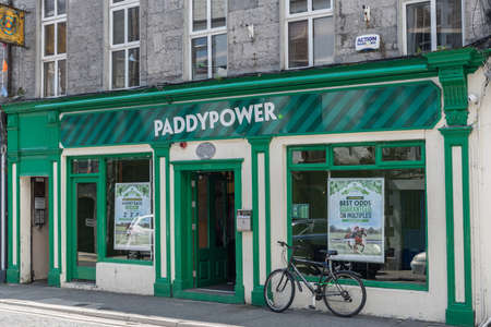 Galway, Ireland - August 5, 2017: The green facade of Paddypower betting company store shows street scene with bicycle, open door and two display windows. Editorial