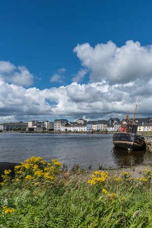 Galway, Ierland - 5 augustus, 2017: Portret van enorme witte cloudscape in blauwe hemel over sectie van de Lange Gangkaai. Vooraan, zwart scheepswrak op donker water daartussenin. Vooraan, wilde gele bloemen en groen.