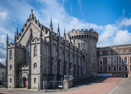 Dublin, Ireland - August 7, 2017: Original church and tower of The Castle, build with dark gray stones, under blue sky with white clouds. Newer side building in back.