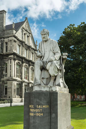 theologian: Dublin, Ireland - August 7, 2017: Graduates Memorial Building with closeup of George Salmon statue at Trinity College. Gray building under blue sky with white clouds. Set in green Library Square with trees. Editorial