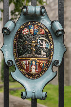 Dublin, Ireland - August 7, 2017: Metal shield fixed on black fence shows colorful Coat of Arms of Saint Patrick Cathedral. Editorial