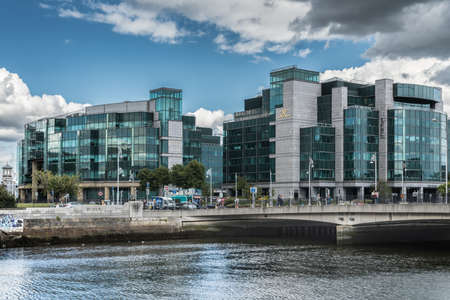 Dublin, Ireland - August 7, 2017: Modern buildings of IFSC House, International Financial Service Center along Liffey River in new financial district. More glass than concrete. Street scene. Editöryel