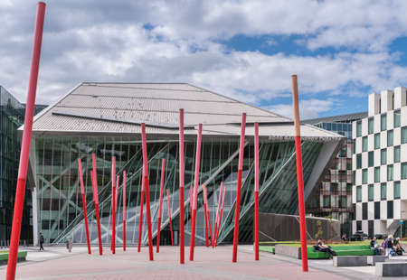 Dublin, Ireland - August 7, 2017: New modern building of Bord Gais Energy Theater on Grand Canal Square with forest of red sticks art composition in front. Glass Triangles and other shapes. Street scene.