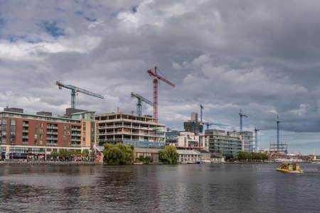 Dublin, Ierland - 7 augustus 2017: Hanover Quay met highrises in aanbouw door zes hoge kranen onder zware luchten. Grand Canal vooraan.