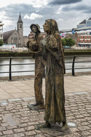 Dublin, Ireland - August 7, 2017: Great Irish Famine bronze statue set on Custom House Quay along Liffey River in Docklands.. Two figures, male and female, out of six plus dog total. Editorial