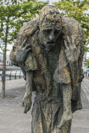 Dublin, Ireland - August 7, 2017: Great Irish Famine bronze statue set on Custom House Quay along Liffey River in Docklands. One slender male figure carries dead female. Green trees.