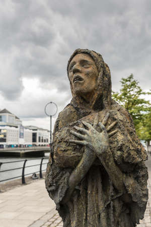 Dublin, Ireland - August 7, 2017: Great Irish Famine bronze statue set on Custom House Quay along Liffey River in Docklands. One slender female figure. Green trees.