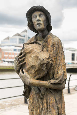 Dublin, Ireland - August 7, 2017: Great Irish Famine bronze statue set on Custom House Quay along Liffey River in Docklands. One slender male figure.