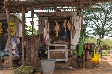 Mysore, India - October 27, 2013: Along the road, brown dilapidated butcher stall sells lamb and chicken meat off hooks in open air with insects around. Merchants present. Green background.