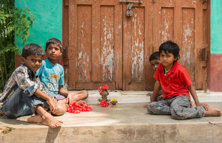 Mysore, India - October 27, 2013: Four small kids in colorful shirts sit and play in front of house with clay figurines looking into camera. Brown and green background.