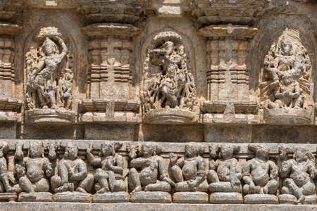 gods: Mysore, India - October 27, 2013: Stone frieze with heavily damaged statues on outside wall of central shrine, called Trikuta, at Chennakesave temple in somanathpur. Line of sitting men, deities. Stock Photo
