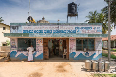 Mysore, India - October 27, 2013: Simple fresh milk collection building of government company in hamlet of Kethupura. Messages on wall. People, black water tank and empty milk canisters. Under blue sky.