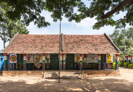 Mysore, India - October 27, 2013: Government higher primary school building under red tiled roof and with walls painted with colorful images and texts of basic knowledge. Under bluish sky and green trees Editorial