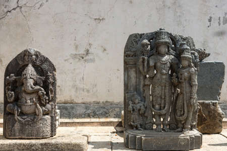 Mysore, India - October 27, 2013: Unearthed gray stone statues on display on the grounds of the Chennakesava Temple in Somanathpur. Set against  filthy white wall showing Nandi and Vishnu with consort