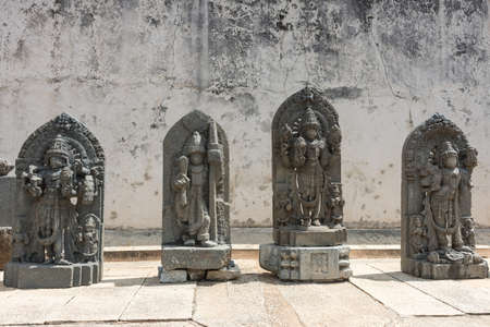 Mysore, India - October 27, 2013: Four gray stone statues on display on the grounds of the Chennakesava Temple in Somanathpur. Set against  filthy white wall showing Vishnu and other deities.