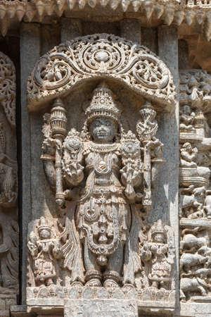 Mysore, India - October 27, 2013: Closeup of brown stone, well preserved Lord Vishnu in full regalia statue on outside wall of Trikuta shrine. Editorial