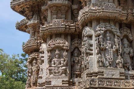 Mysore, India - October 27, 2013: Several brown stone, well preserved Lord Vishnu in full regalia statues on outside wall of Trikuta shrine.