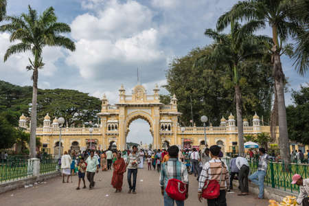 Mysore, India - October 27, 2013: Yellow South entrance gate to Mysore Palace domain among green trees and under blue sky with white clouds. Many people with colorful clothes in photo.