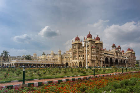 Mysore, India - October 27, 2013: Wide shot out of garden of South and East facades of Mysore Palace under cloudscape. Yellow building with towers and maroon domes. Flowers up front. Editorial