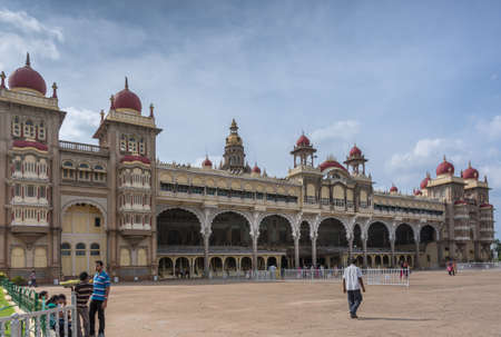Mysore, India - October 27, 2013: Wide shot of East facade of Mysore Palace under cloudscape. Beige building with towers and maroon domes. Seen from Southeast corner.