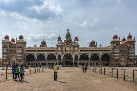 Mysore, India - October 27, 2013: Wide frontal shot of entire East facade of Mysore Palace under cloudscape. Beige building with towers and maroon domes. Central tower with golden domes as well.
