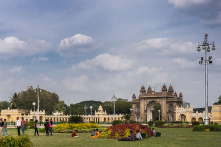 Mysore, India - October 27, 2013: Brown stone main East Gate to Mysore Palace with yellow side buIldings under cloudscape. Shot from Southwest of garden. Visitors add colors.