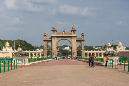 Mysore, India - October 27, 2013: Brown stone main East Gate to Mysore Palace with entire yellow side buIldings under cloudscape. Visitors add colors. Editorial